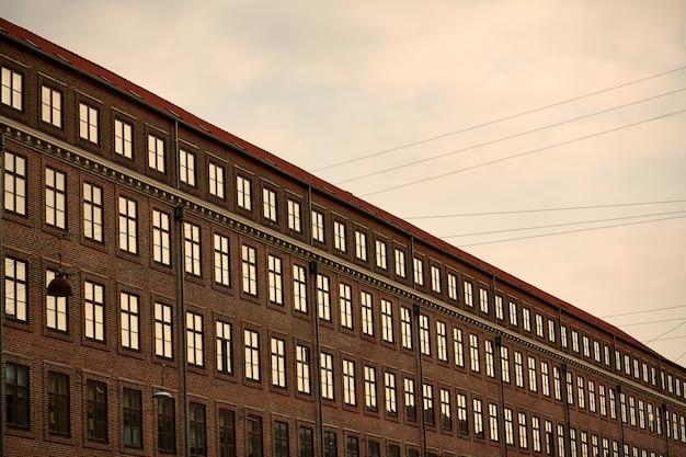Grand bâtiment moderne marron avec des fenêtres sous un ciel nuageux pendant le coucher du soleil