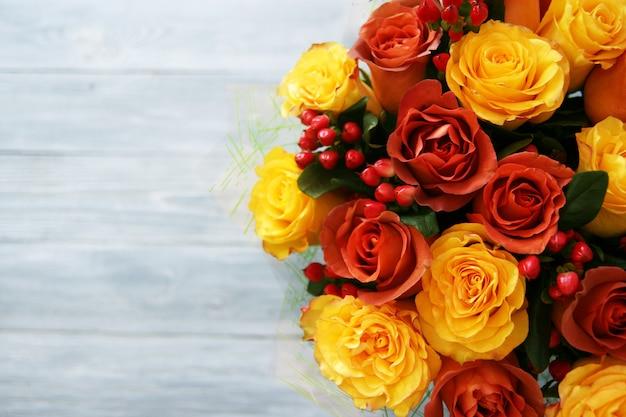Un grand beau bouquet de roses jaunes et rouge-orange et de baies sur un bois gris