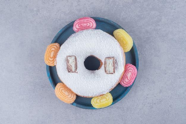 Grand beignet garni de morceaux de chocolat et entouré de marmelades sur une surface en marbre