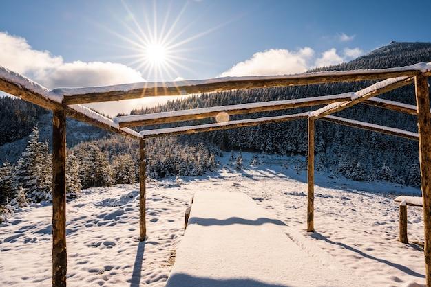 Un grand belvédère non couvert au sommet de la montagne se dresse sur une prairie blanche couverte de neige baignée de la lumière du soleil froid et brillant des carpates