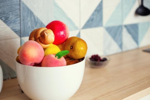 Un grand bol de fruits et légumes se dresse sur la table de la cuisine, l'arrière-plan devient flou
