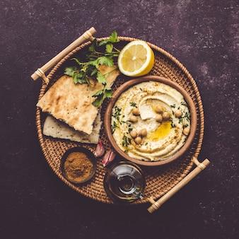 Grand bol de houmous maison garni de pois chiches, de poivron rouge, de persil et d'huile d'olive