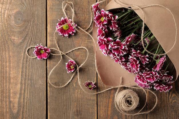 Un grand bouquet de fleurs d'automne de chrysanthèmes en papier kraft sur une table en bois marron