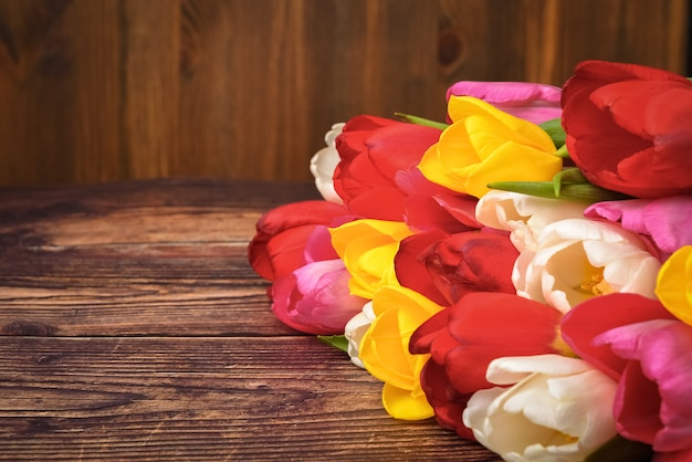 Grand bouquet lumineux de tulipes multicolores sur des planches en bois de couleur brun foncé.