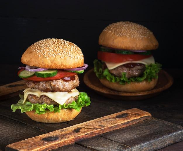 Grand burger avec deux côtelettes frites, du fromage et des légumes