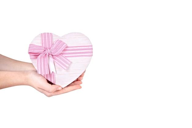 Un grand cadeau en forme de coeur dans une main sur un fond blanc et copiez l'espace