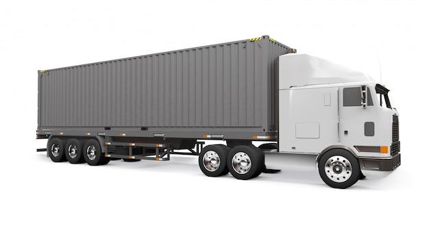 Un grand camion rétro blanc avec une partie couchage et une extension aérodynamique porte une remorque avec un conteneur maritime