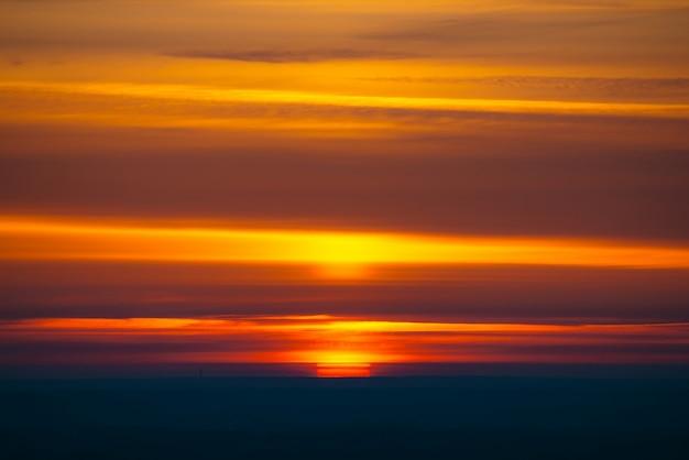 Un grand cercle de soleil rouge s'élève derrière l'horizon sombre sur des nuages multicolores aux nuances chaudes. beau fond de l'aube sur un ciel nuageux pittoresque. soleil au centre.