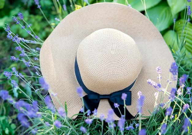 Grand chapeau de paille dans les buissons de lavande. concept d'été romantique.