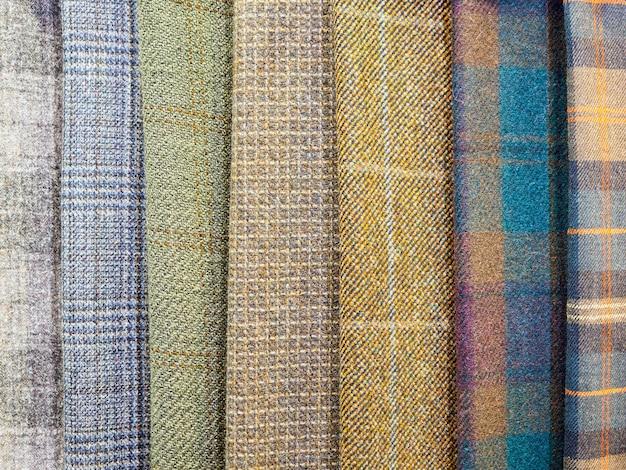 Un grand choix de tissus à carreaux lumineux dans le magasin de tissus. gros plan d'échantillons de tissus cellulaires.