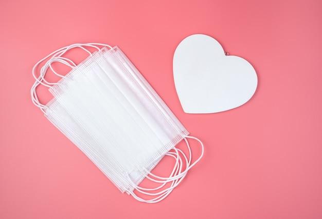Grand coeur blanc et masque protecteur sur fond rose. vue de dessus, fond romantique. concept 14 février.