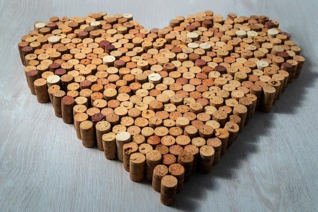Grand coeur fait de bouchons de liège sur fond de bois, concent de conception de vin