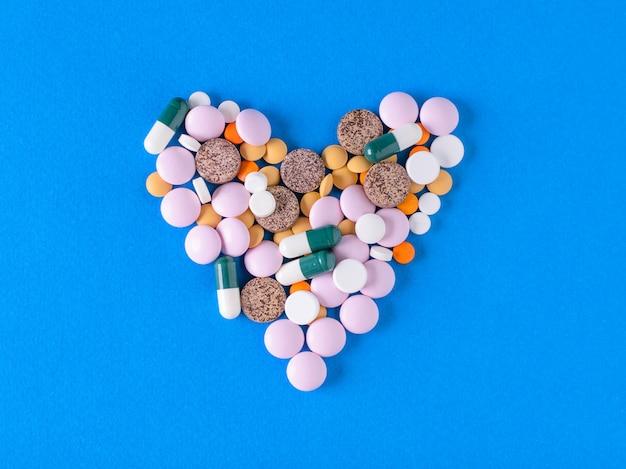 Un grand coeur de pilules colorées sur fond bleu.