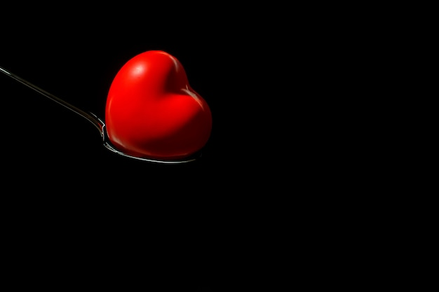 Grand coeur rouge sur une cuillère en métal sur fond noir