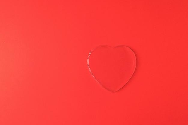 Un grand coeur transparent sur fond rouge vif. un symbole d'amour et de vie.