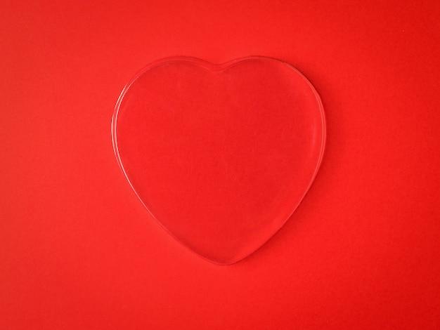 Un grand coeur en verre sur fond rouge. un symbole d'amour et de vie.