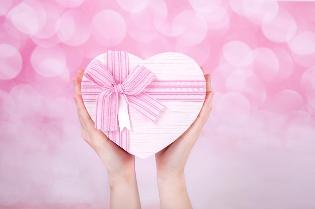 Grand coffret cadeau en forme de coeur avec un arc rose dans une mains sur fond blanc, vue du dessus