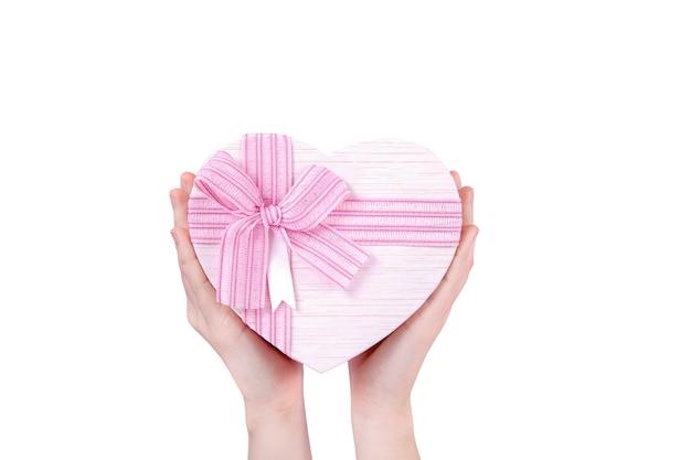 Grand coffret cadeau en forme de coeur avec un noeud rose dans vos mains sur fond blanc, vue du dessus