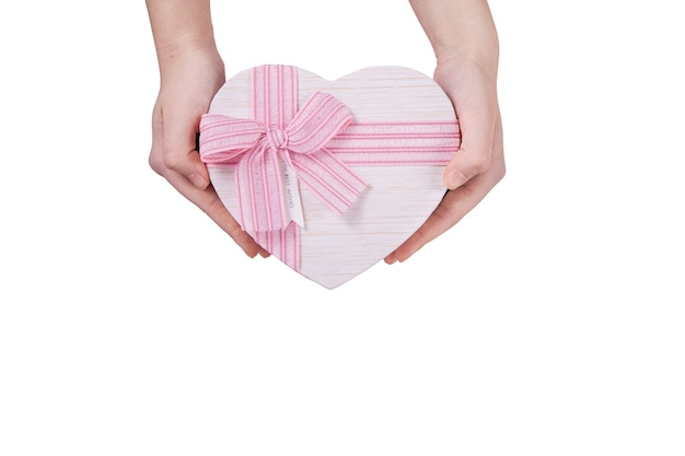 Grand coffret cadeau en forme de coeur avec un noeud rose dans vos mains sur fond blanc