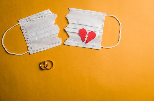 Grand concept de divorce en quarantaine en raison de la pandémie de coronavirus de 2019. masque facial coupé en deux avec des anneaux de mariage.