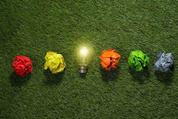 Grand concept avec du papier de bureau froissé et une ampoule debout sur la table