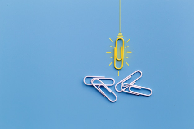Grand concept d'idées avec un trombone, pensée, créativité, ampoule sur fond bleu, nouveau concept d'idées.