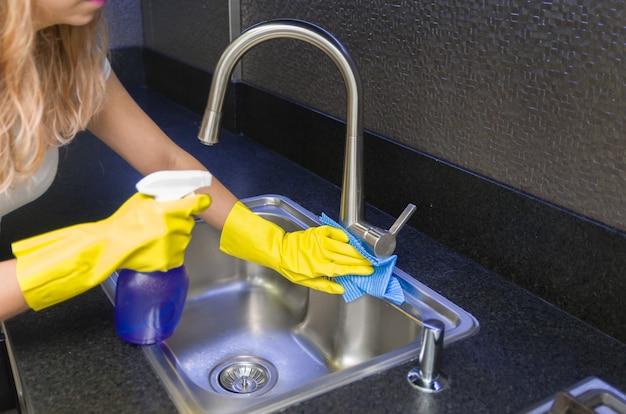 Grand concept de nettoyage domestique, femme nettoyant l'évier