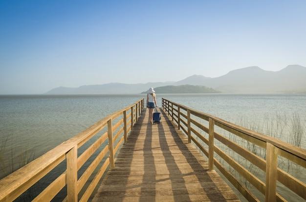 Grand concept de vacances. jeune femme tenant sa valise, attendant le bateau sur le quai