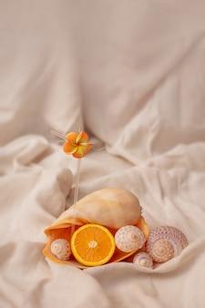 Grand coquillage sous forme de verre à cocktail avec un fond orange à l'intérieur de l'été