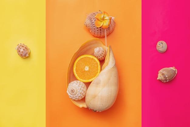 Grand coquillage sous forme de verre à cocktail avec une orange à l'intérieur sur fond orange fond d'été