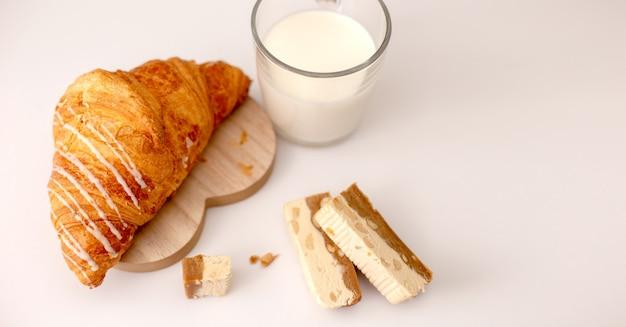 Grand croissant et tasse en verre avec du lait se tiennent sur un tableau blanc