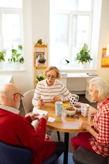 Grand divertissement. gens âgés sympas assis autour de la table tout en jouant aux cartes ensemble