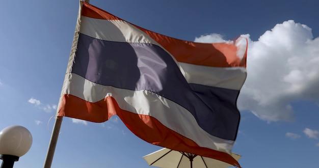 Grand drapeau de la thaïlande flottant au vent contre des nuages blancs