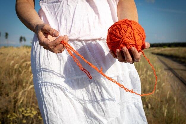 Grand écheveau orange de fil entre les mains des femmes