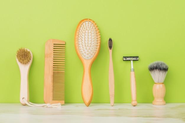 Un grand ensemble d'accessoires pour hommes pour les soins de la peau et des cheveux sur fond vert.