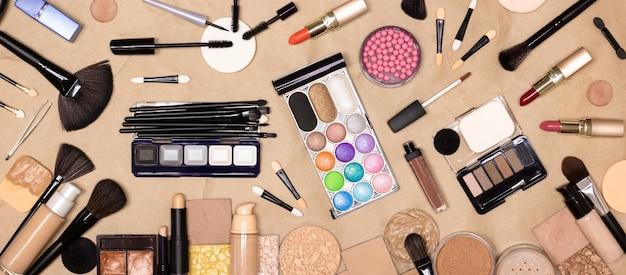 Grand ensemble de divers produits de maquillage et accessoires sur papier kraft table de maquillage vue de dessus à plat