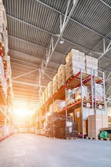 Grand entrepôt industriel. longues étagères avec une variété de boîtes et de conteneurs. lumière du soleil éblouissante.