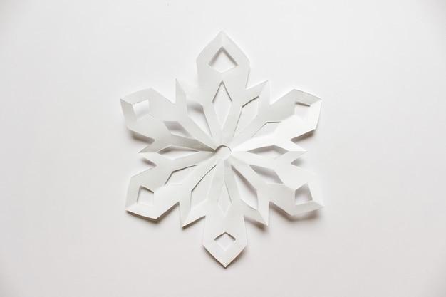 Grand flocon de neige blanc sur fond blanc