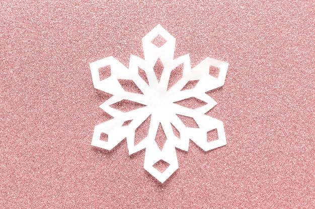 Grand flocon de papier blanc sur fond de paillettes roses