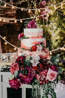 Grand gâteau de mariage décoré de fleurs rouges.