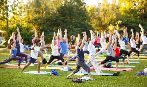 Grand groupe d'adultes assistant à un cours de yoga à l'extérieur dans le parc