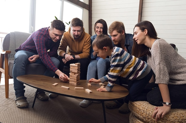 Un grand groupe d'amis joue à des jeux de société, une compagnie joyeuse à la maison. photo de haute qualité