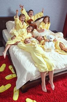 Grand groupe d'amis prenant le temps de goog sur le lit