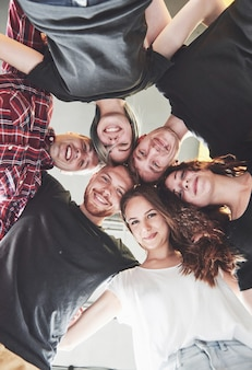 Un grand groupe d'amis souriants étreignant ensemble.