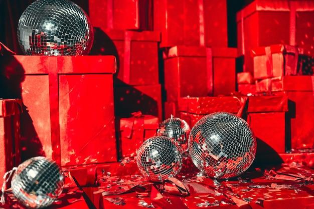 Un grand groupe de cadeaux de noël emballés dans du papier d'emballage rouge coloré avec des rubans et des arcs, sur fond rouge avec des boules disco et du métaphane. photozone cadeau nouvel an