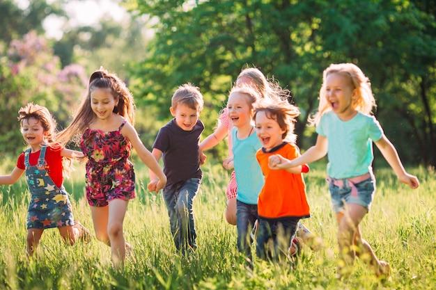 Grand groupe d'enfants, d'amis garçons et filles courir dans le parc sur une journée d'été ensoleillée en vêtements décontractés.