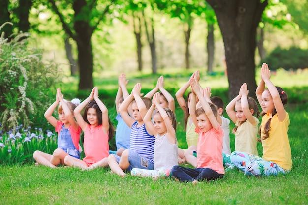 Un grand groupe d'enfants pratiquant le yoga dans le parc assis sur l'herbe.