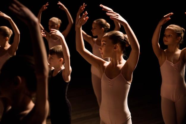 Un grand groupe d'enfants répétant et dansant le ballet.
