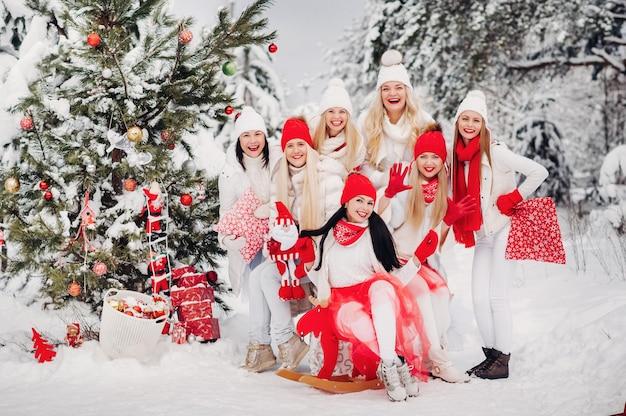 Un grand groupe de filles près de l'arbre de noël dans la forêt d'hiver avec des cadeaux.