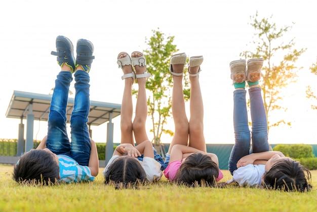 Grand groupe de joyeux enfants souriants asiatiques amis enfants couché sur l'herbe et la jambe levée dans le ciel ensemble dans le parc sur l'herbe verte le jour d'été ensoleillé.